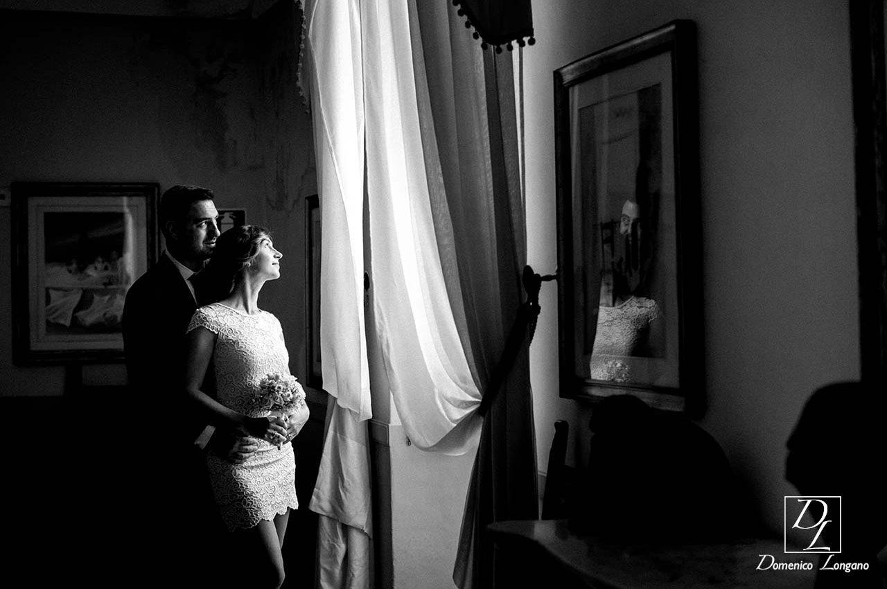 sposi abbracciati alla finestra in bianco nero